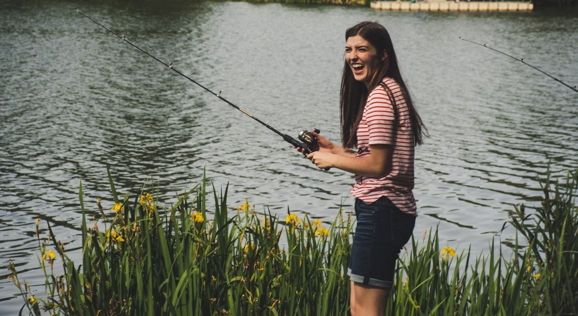 Woman, holding fishing pole in front of pond