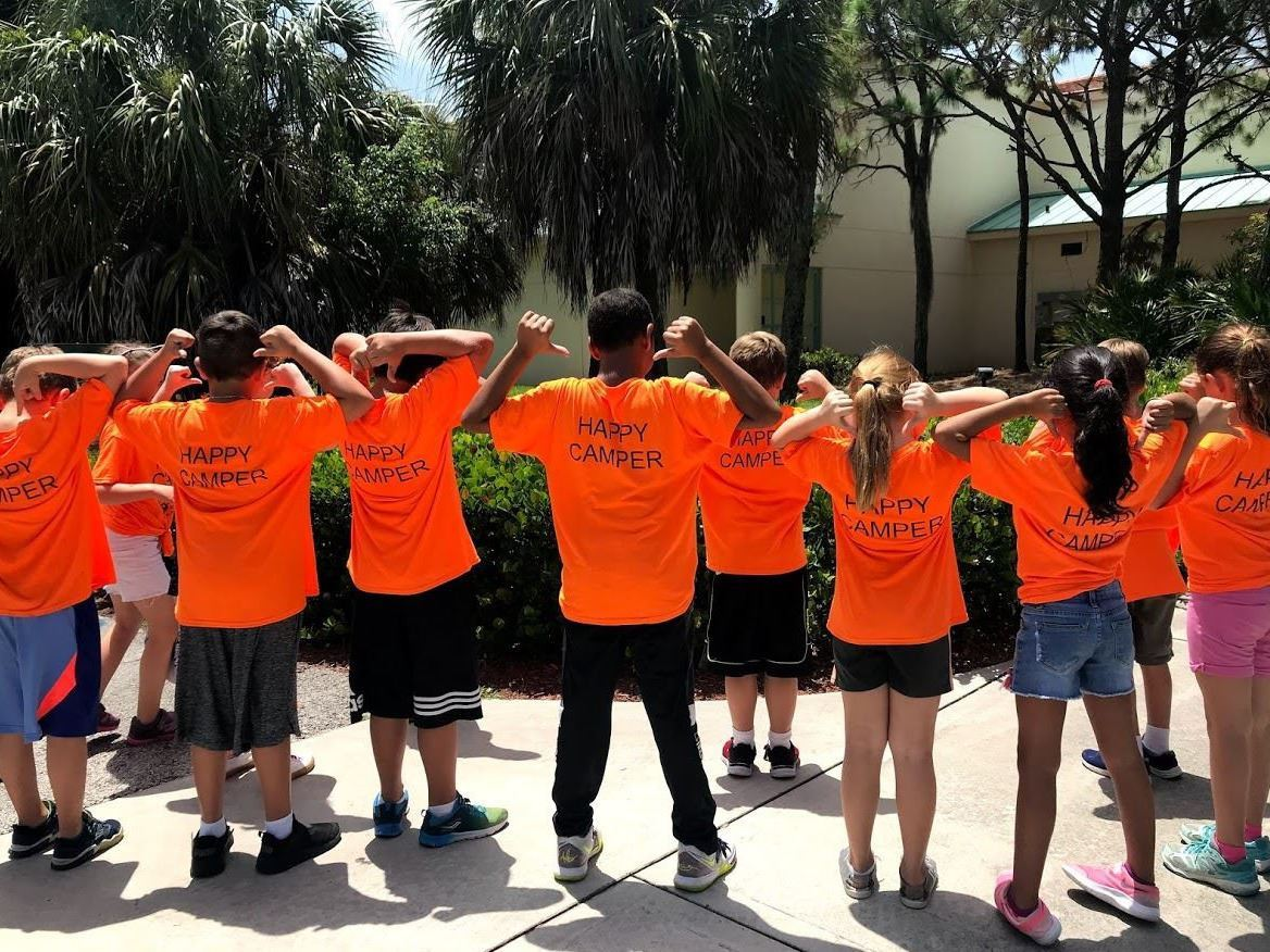"8 campers pointing to the back of their orange shirts that say ""Happy Camper"""