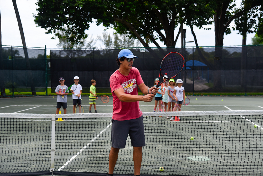 instructor teaching tennis to kids